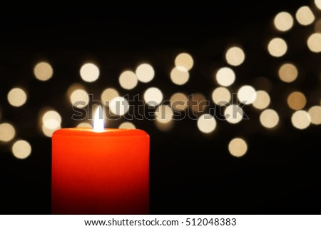 red candle with christmas lights bokeh and dark background
