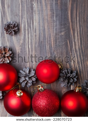 Red christmas balls and pine cones on the wooden table, up view