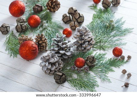 red christmas balls, pine and cypress cones with twigs on white wood table