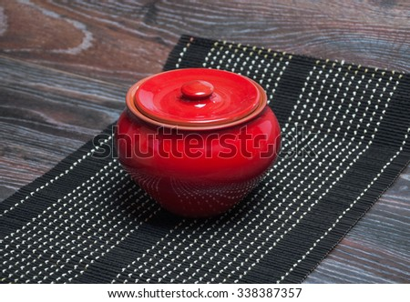 Red clay pot with lid on the table