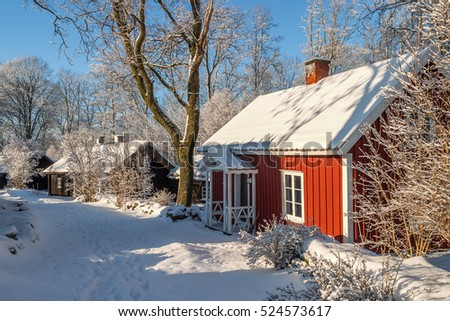 Red cottage on a path in the wintry landscape