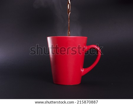 Red cup with hot coffee on a black background