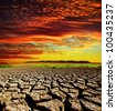 red dramatic sunset over dry cracked earth - stock photo