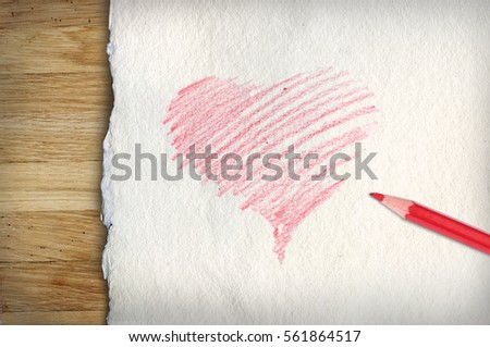 Red drawn heart and red pencil on old paper and wooden background