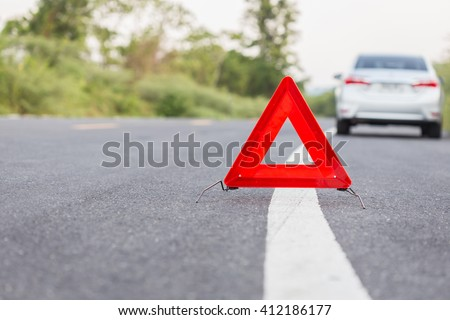 Red emergency stop sign and broken silver car on the road.