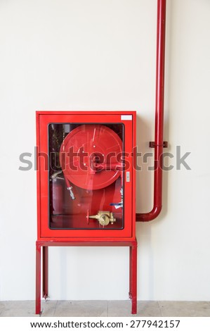 Red extinguisher on white wall