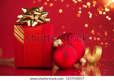 Red gift box with ornaments and ribbons on red holiday background with twinkle bokeh light. Merry christmas card. Winter xmas theme
