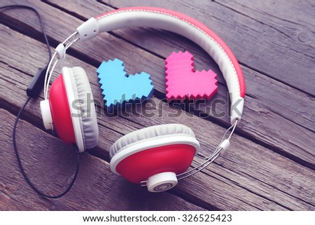 Red headphones near hearts on wooden background