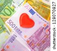Red heart on euro money (Love for Money concept). - stock photo