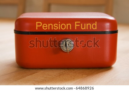 Red metal pension fund savings tin on a wooden surface