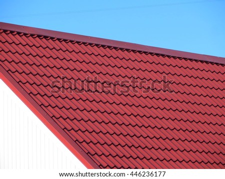 Red modern roof covered with tile effect PVC coated metal roof sheets against a blue sky