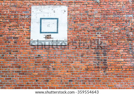 red old brick wall with basketball plate for background.