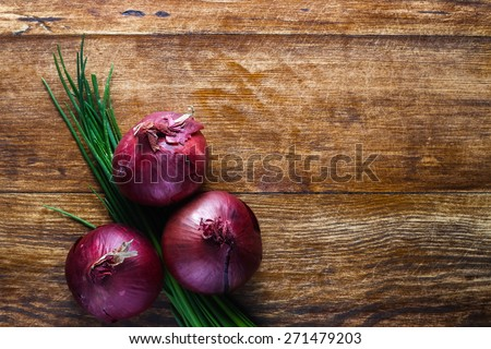 Red onions and bunch chives composition lying on the wooden table