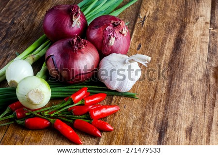 Red onions chili peppers garlic and bunch chives composition lying on the wooden table