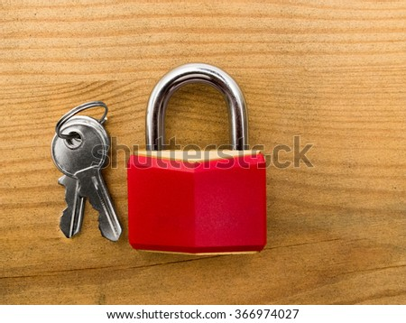 Red padlock with keys on wooden background