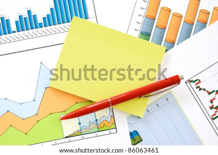 red pen and yellow memo over financial charts