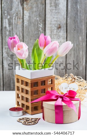 Red pink yellow tulips and gift box with red ribbon on a white painted wooden background and empty space for text. Top view with copy space