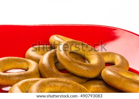 red plate with set small bagels on a white background