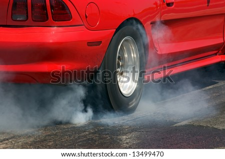 Red race car burns rubber off its tires in preparation for the race