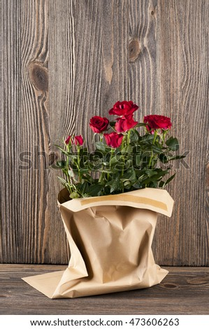 Red rose flowers in paper-bag on a wooden background. Studio shot.