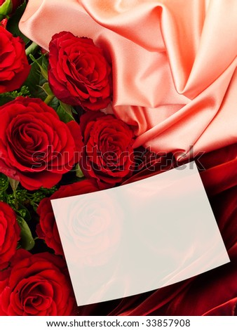 red roses with white greeting card at fabric