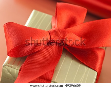Shutterstocklvvgift bow red satin bow on a gift box in golden paper cover close up negle Image collections