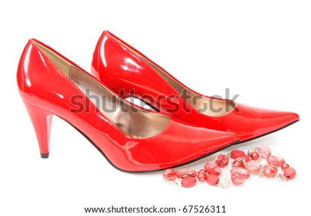 Red shoes with costume jewellery on a white background it is isolated.