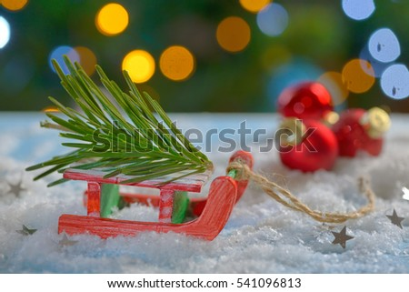 Red sleigh toy and Christmas tree on fake snow