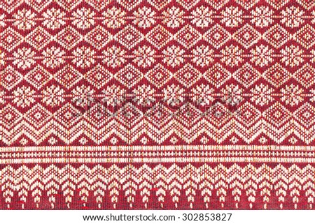 Red thai silk fabric pattern background. Old handmade.