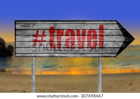 Red The word with hashtag TRAVEL wooden sign with on a beach background
