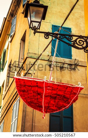 Red umbrella hanging on the street. Decoration on holidays in Italy.