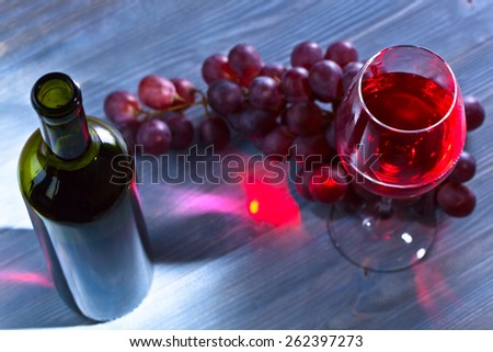 red wine and grapes on old wooden table