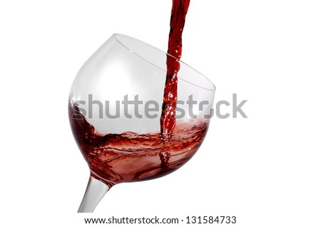 red wine being poured in a tilted wine glass isolation on white