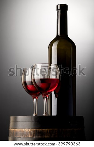 Red wine bottle and wine glasses on wodden barrel isolated on black