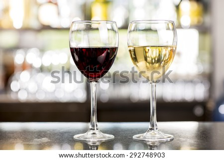 Red wine glass and two bread pieces on a table