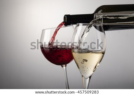 Red wine glass and white wine glass poured from bottles on white with copy space.