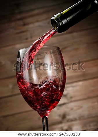 Red wine pouring in a glass on wood background