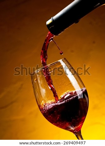 Red wine pouring with a drop