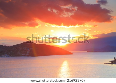 Reddish clouds and sun over the Mediterranean sea