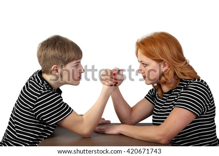 Redhead woman and teenage boy in similar t-shirts fight on hands isolated on white background in square - mother and son armrestling - solution of disagreements in the family