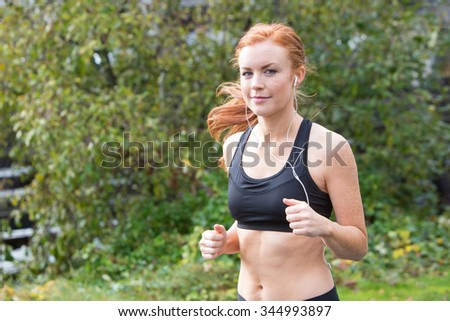 redhead woman running outside on a trail