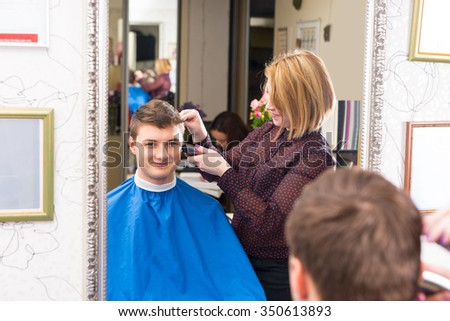 Reflection in Mirror of Smiling Young Man Having Hair Cut and Styled by Blond Female Stylist in Salon