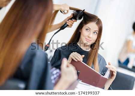 Reflection of beautician doing hair style for woman in hairdress salon. Concept of fashion and beauty