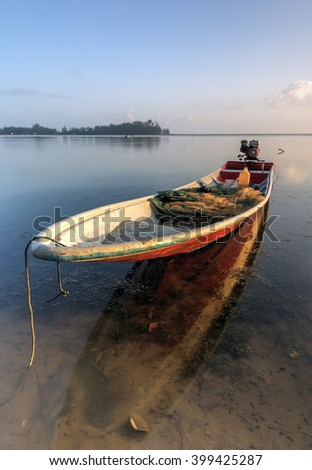 Reflections of a fisherman's boat at Jubakar Beach, Tumpat, Kelantan, Malaysia. Taken during sunrise using slow shutter. Motion blur and soft focus due to long exposure.