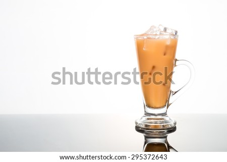 Refreshing ice cold tea with milk in transparent glass flushed right