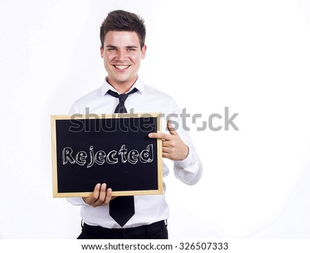 Rejected - Young smiling businessman holding chalkboard with text
