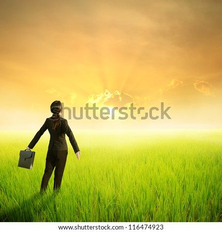 Relax business woman holding bag in green rice field and sunset