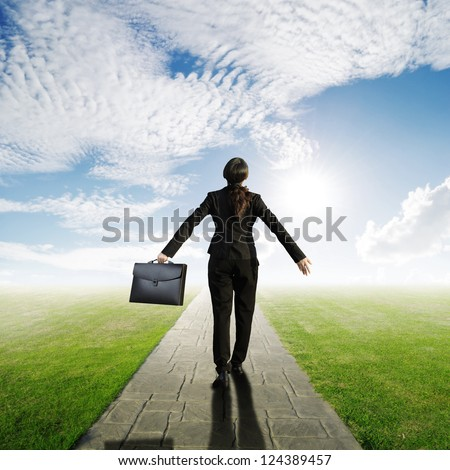 Relax business woman holding bag on Concrete road in Grass fields and sun sky