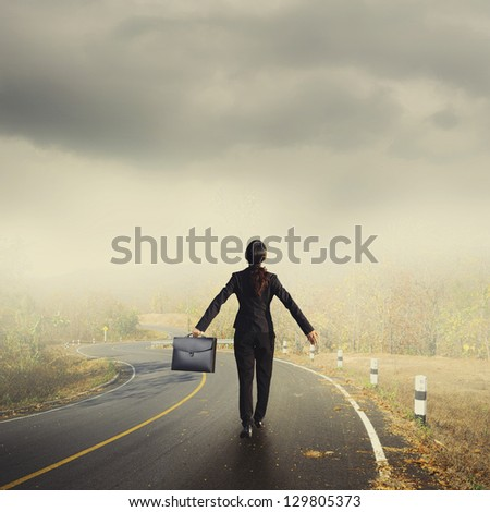 Relax business woman holding bag on Country road and rainclouds