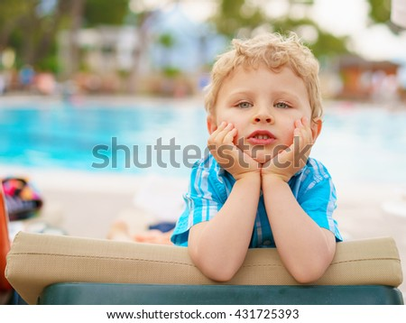 Relaxed boy sitting on a beach couch, clutching his cheeks. Resort pool in the blurry background.